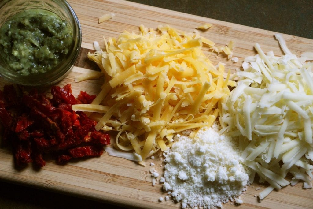 Grated cheeses, pesto and sundried tomatoes