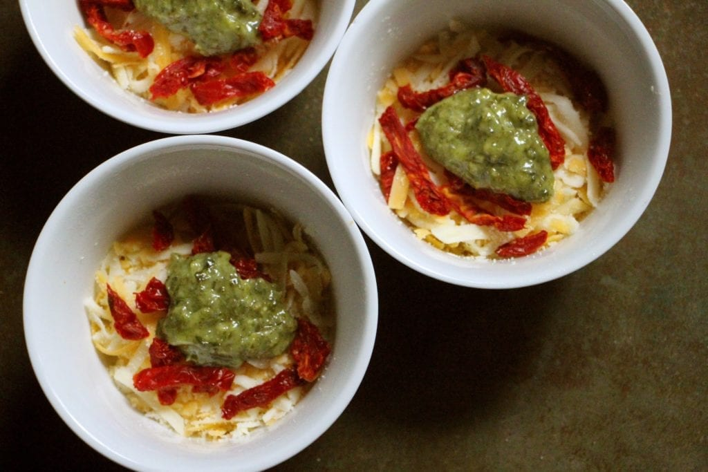 Divide cheese, pesto, and tomatoes among the ramekins